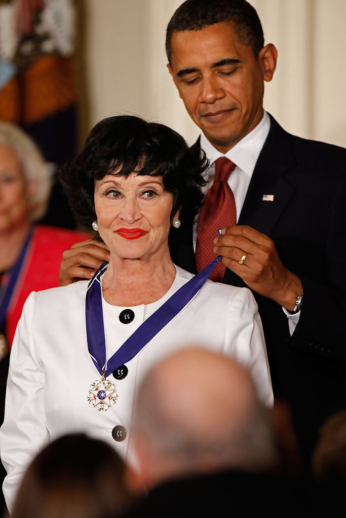 Barack Obama places a medal with a blue ribbon on Chita Rivera.